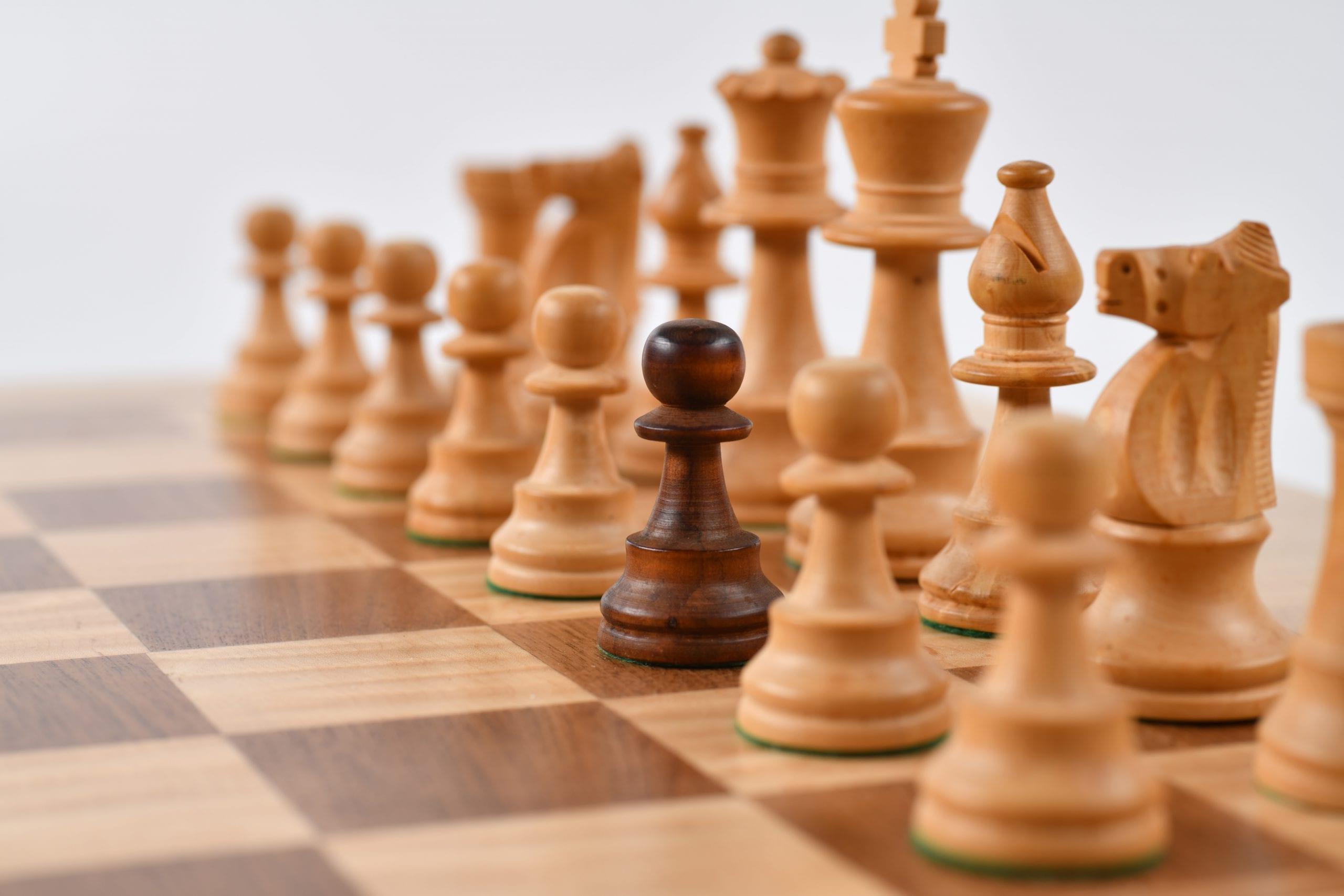 One Black Pawn around a White Set of Chess Pieces