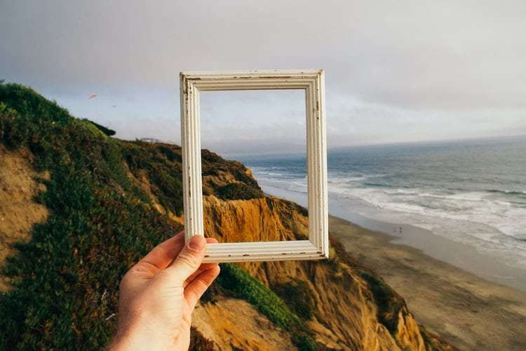 a hand holding an empty picture frame by the coast